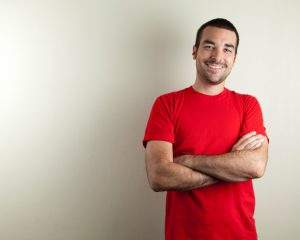"""An ordinary man with red t-shirt on beige background, smiling. Copy space."""