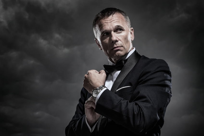 A handsome mature male secret agent, bodyguard, spy, or security staff dressed in an elegant tuxedo and bow tie as he adjusts his watch or cuff links on a stormy night with cloudy sky in the background.