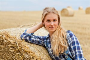 Beautiful young woman standing on field and leaning on roll bale of straw. She contentedly looking into the camera. Shallow DOF. Shooting with the Canon EOS 5D Mark II.
