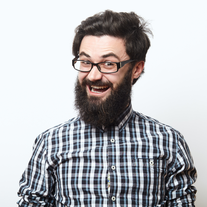 Closeup portrait of young bearded hipster man with shirt and glasses over a white background