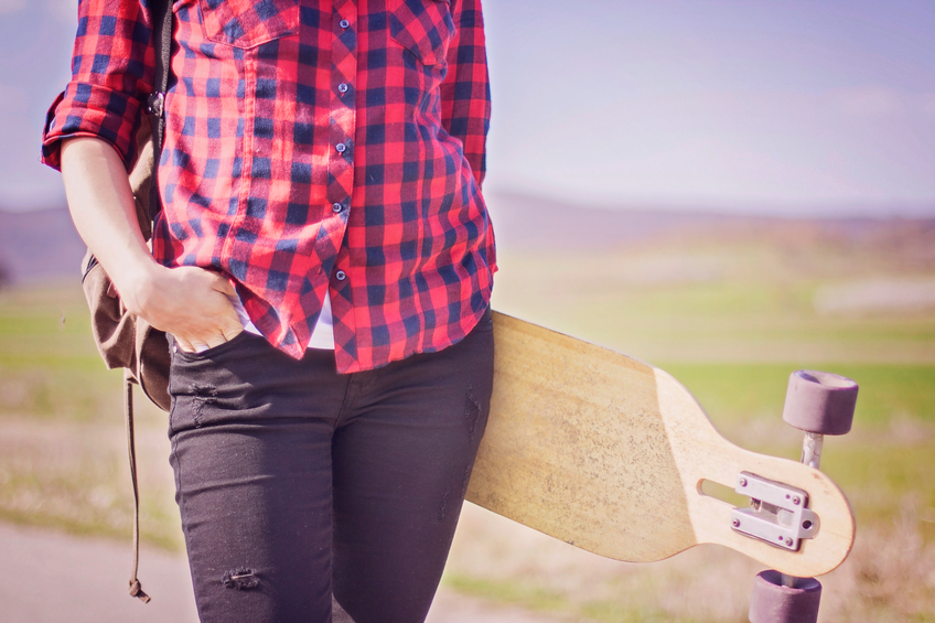 Girl in plaid shirt holding skateboard